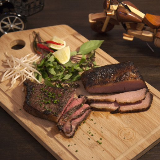 A cutting board featuring two cuts of red meat with leafy greens, limes, and sprouts on the side