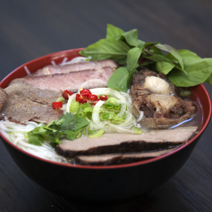 A bowl of pho containing noodles, slices of red meat, green onions, and other ingredients