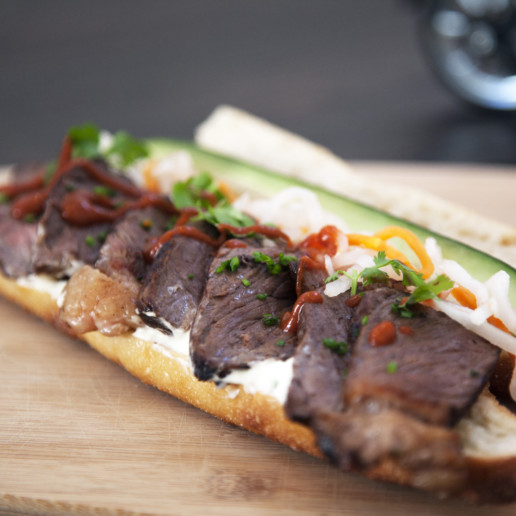 A sandwich in a roll containing red meat and various toppings
