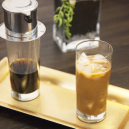 A glass of iced coffee sits next to a coffee press