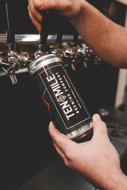 A Ten Mile Brewing Company tall can being filled up from a beer tap