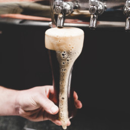 A tall beer glass being poured into from a beer tap, with foamy beer leaking down the side of the glass