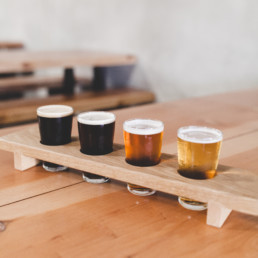 A flight of four beers, two dark and two light in a wooden drink holder