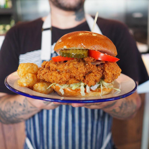 A man holding a plate containing a fried chicken sandwich on a bun with toppings like pickles, slaw, and tomatoes with tater tots on the side