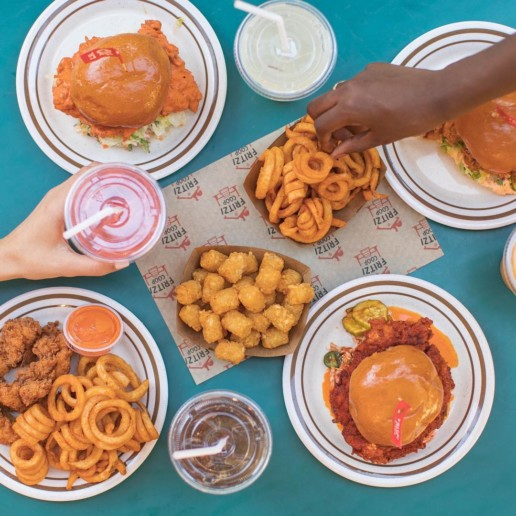Multiple plates featuring tater tots, curly fries, various fried chicken sandwiches, and drinks in plastic cups with straws