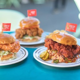Three plates featuring fried chicken sandwiches with Fritzi Coop toothpick flags popping out from the top of the sandwiches.