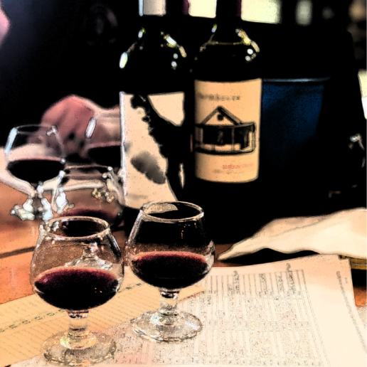 Glasses of red wine and wine bottles decorate a table with sheets of paper on it