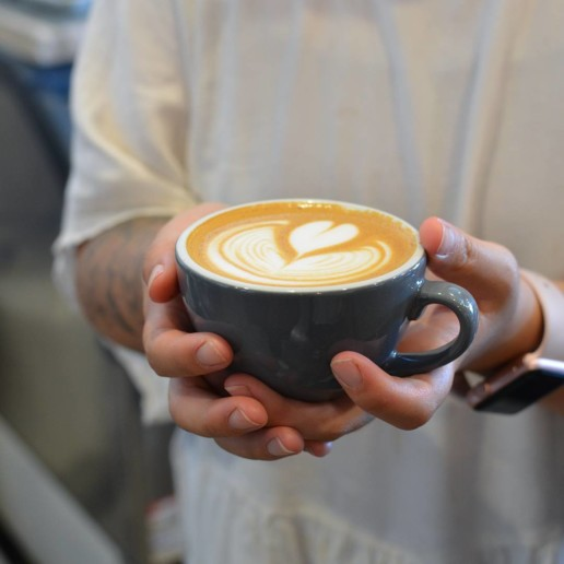 A man holding a steamed coffee drink