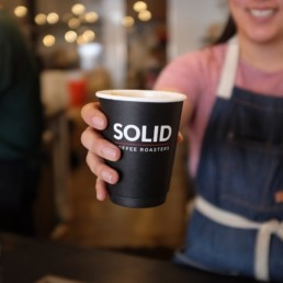 A cup of coffee in a Solid Coffee Roasters cup