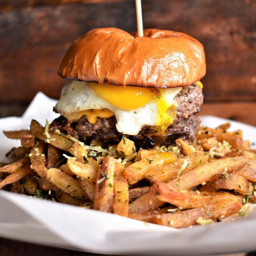 A burger topped with an egg sits on a plate surrounded by fries