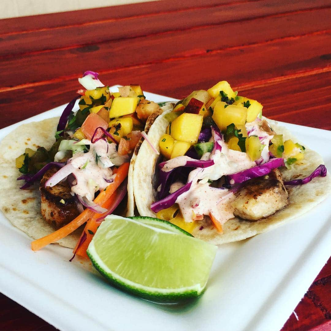 Two tacos on a plate with chicken topped with coleslaw and fruit, with lime on the side
