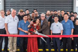 The co-founders of SteelCraft prepare to cut the ribbon at SteelCraft Bellflower's grand opening event, flanked by SteelCraft and vendors' employees