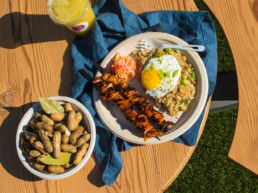 A wooden table featuring a bowl of peanuts, a plate with meat skewers, an egg, and rice, and a lemonade