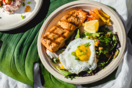 A plate featuring a piece of grilled fish, an over easy egg, and leafy greens beneath it