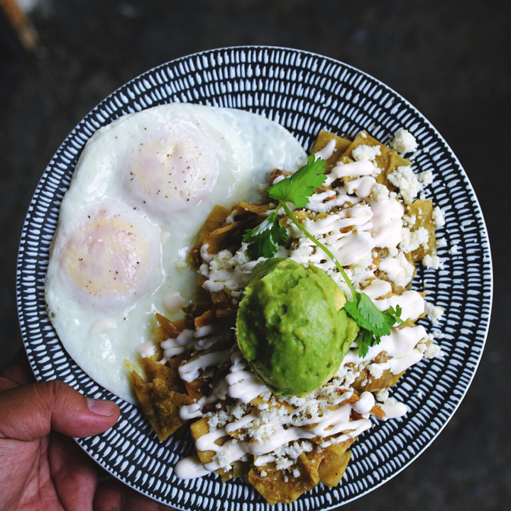 A plate featuring two cooked eggs, chips, and guacamole all covered in cheese and a sauce
