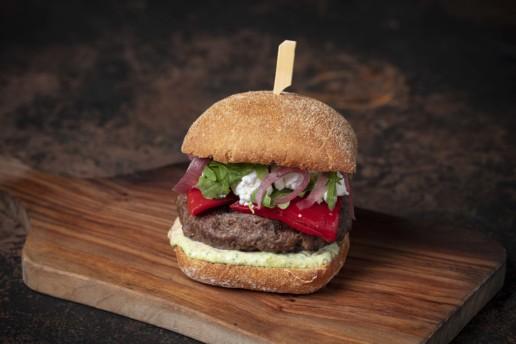 A burger on a sourdough bun on top of a wooden platter