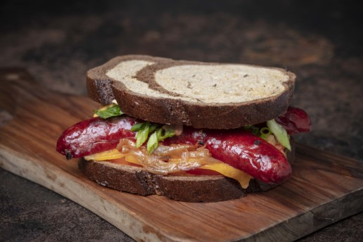 A hot dog sandwich on a wooden platter