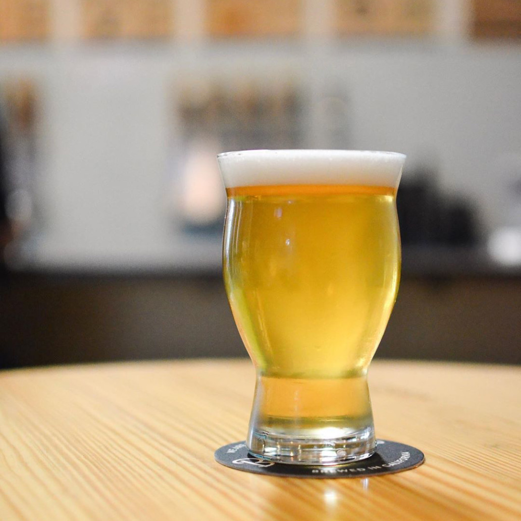 A glass of a golden ale beer on a Beachwood Brewing coaster