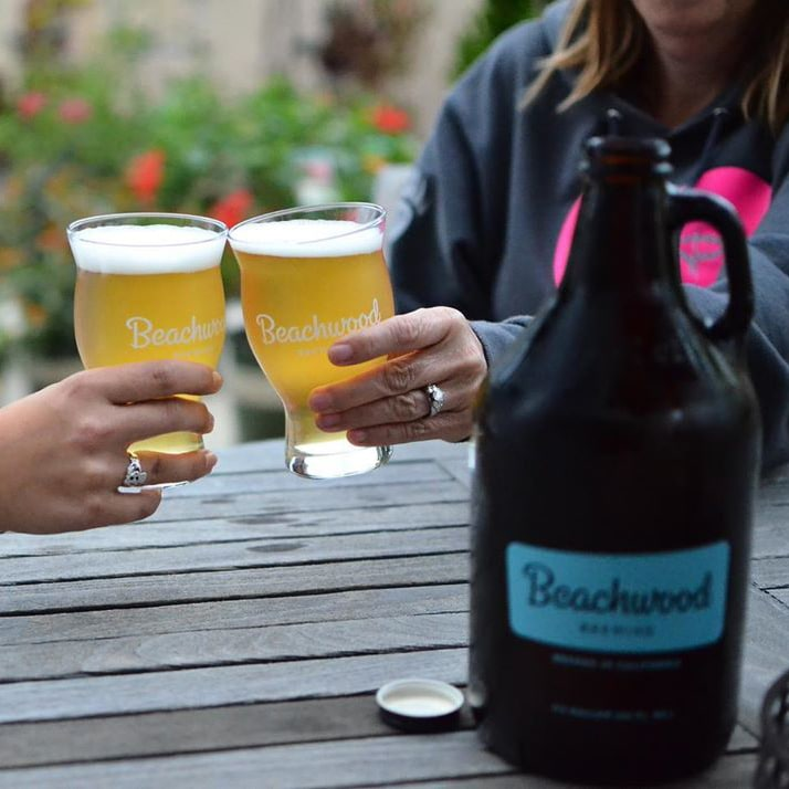 Two people bringing their Beachwood Brewing glasses together in a cheers
