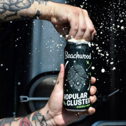 A tall can of Beachwood Brewing's Hopular Cluster being cracked open in someone's hands