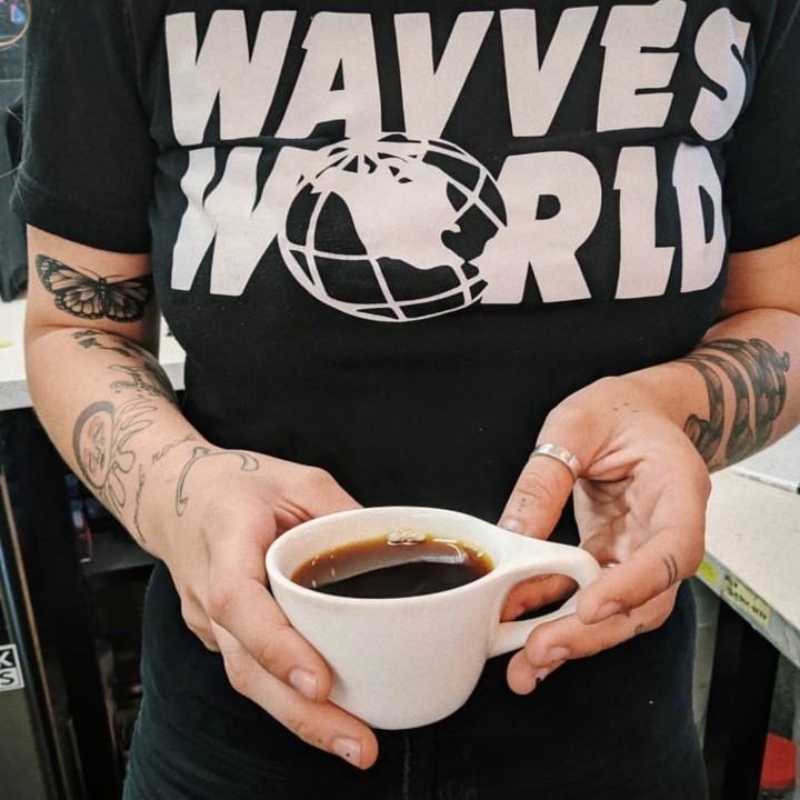 A cup of black coffee from Dark Horse held in someone's hands