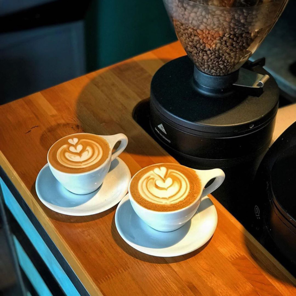 Two foamed coffee drinks on a wooden counter