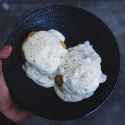 Biscuits smothered in gravy on a black plate.