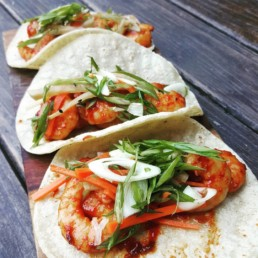 Three tacos in soft tortillas containing shrimp and various vegetables