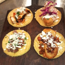 Four different tacos all on corn tortillas with varying ingredients
