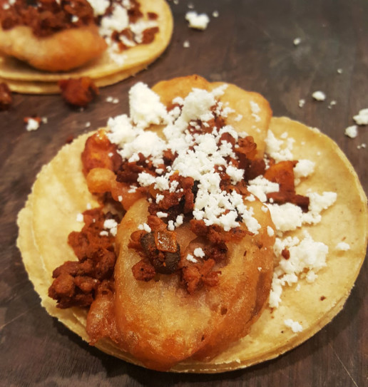 A fried fish taco on a soft corn tortilla topped with feta cheese