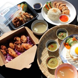 Multiple boxes and plates of food with rice, egg, various kinds of fried chicken, and dipping sauces