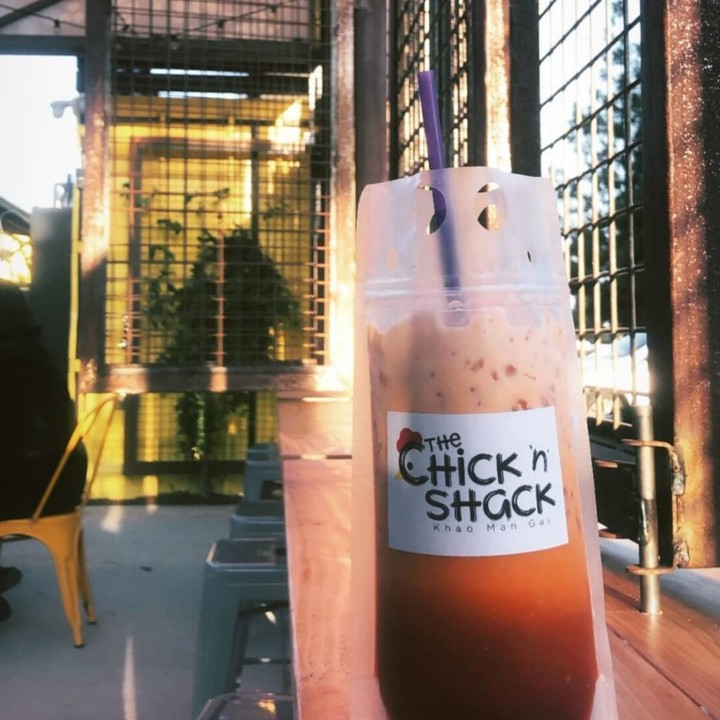 A Chick N Shack Thai iced team in a plastic bag with a straw