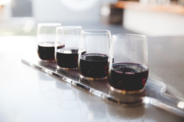 Four glasses of wine sitting in a clear wine flight tray
