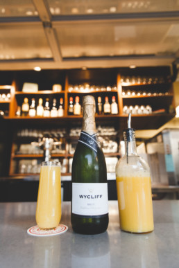 A bottle of champagne flanked by a mimosa to the left on an Off Duty coaster, and on the right, a glass bottle of orange juice.