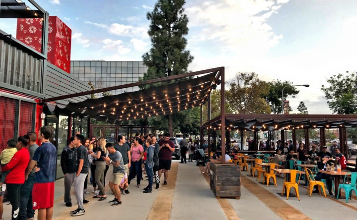 A line of people wait for one of the vendors of SteelCraft Garden Grove as others sit and eat or drink at nearby tables