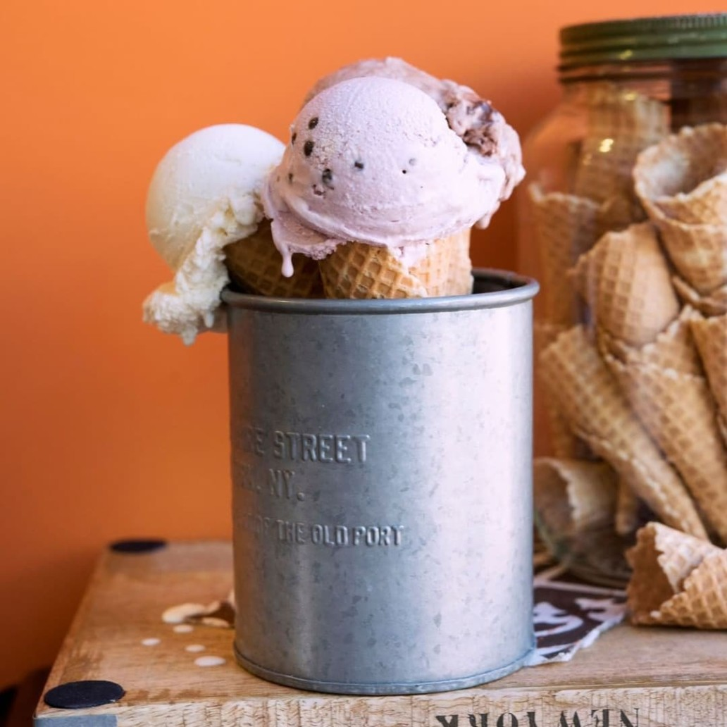Two ice cream cones with scoop of ice cream sitting in a steel container