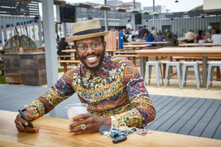 A smiling man wearing a hat and a vibrantly patterned shirt holds a cup of tea in one hand and his phone in the other.