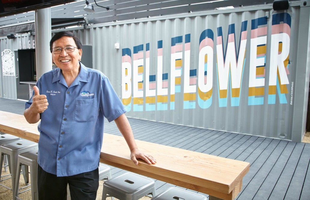 The Mayor of Bellflower poses with a smile and a thumbs-up in front of a steel container with
