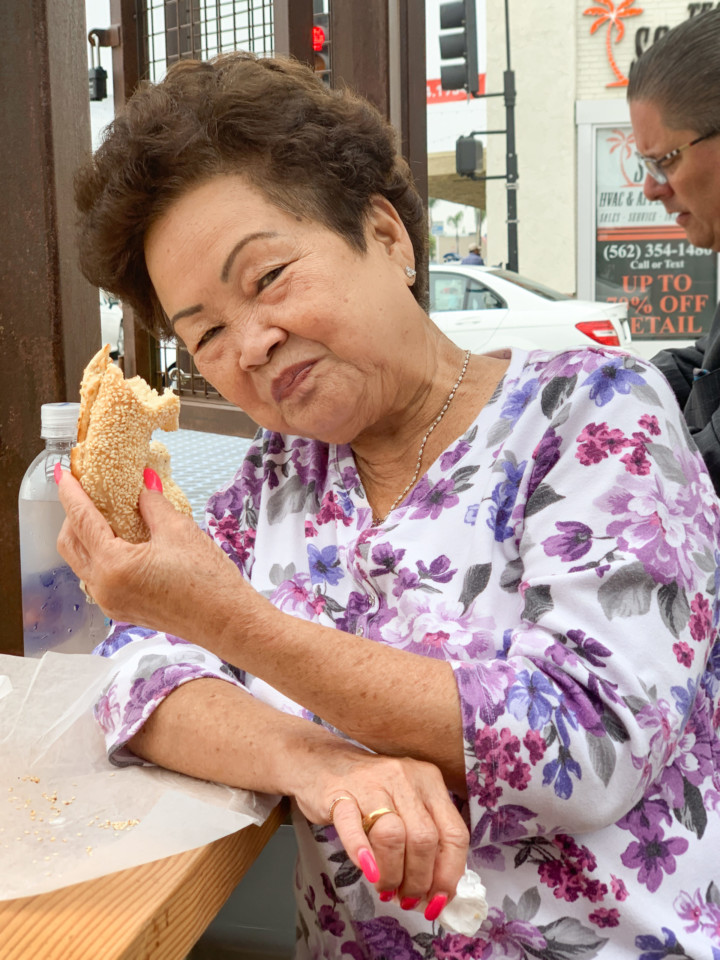 A woman smiling and holding up a half-eaten bagel.
