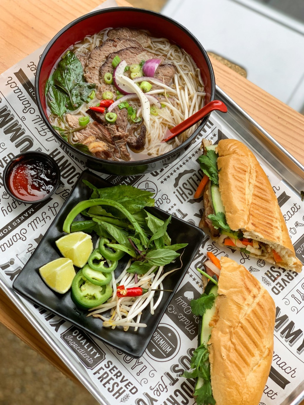 A tray of food featuring a bowl of Pho, a Bahn Mi sandwich, and a plate of vegetables.