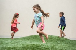 Three children running on grass