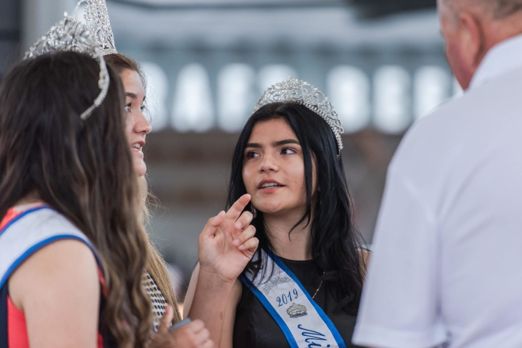 A girl in a tiara looks at her friend