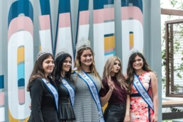 Miss Bellflower candidates smiling in front of a steel container
