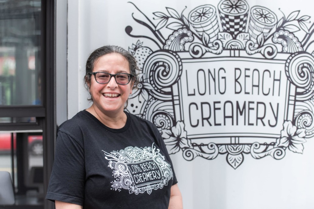 A woman smiling in front of the Long Beach creamery container