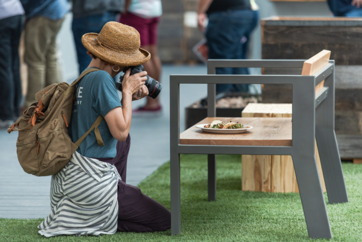 A woman on her knees taking a photo of a plate of tacos