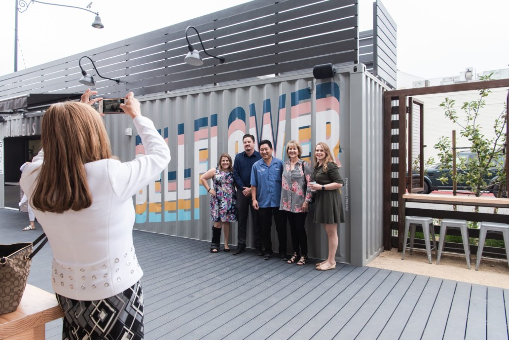 A woman takes a photo on her phone of a group of people in front of a steel container