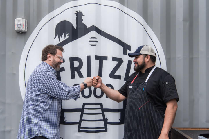 Two men fist bump in front of the Frritzi Coop logo painted on the side of a steel container.