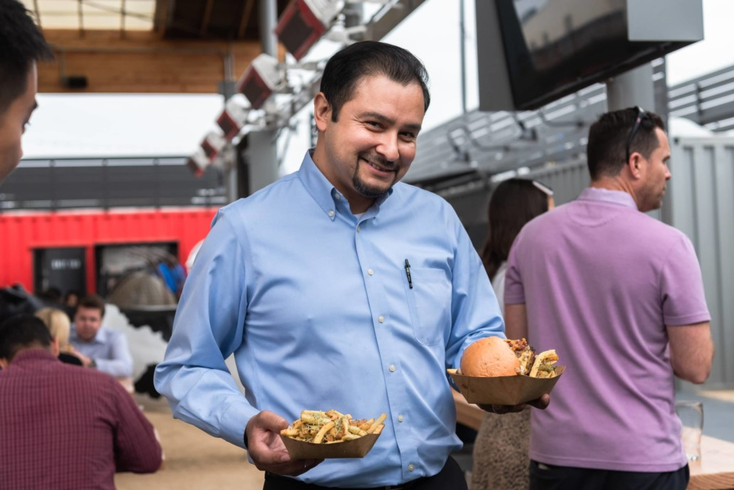 A smiling man holds up a plate of fries in one hand and a fried chicken sandwich in the other.